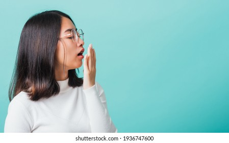 Portrait female bored yawning tired covering mouth with hand, Young beautiful Asian woman sleepy covering opened mouth with palm, studio shot isolated on a blue background