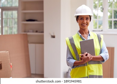 Portrait Of Female Building Surveyor Wearing Hard Hat With Digital Tablet Looking At New Property