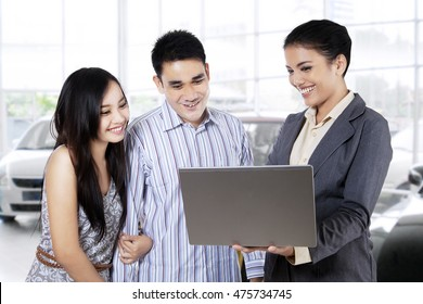 Portrait of a female car seller and her potential buyer looking at laptop in the showroom