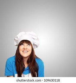 portrait of a female chef looking up on gray background