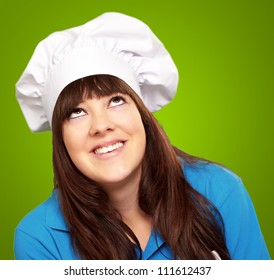 portrait of a female chef looking up on green background