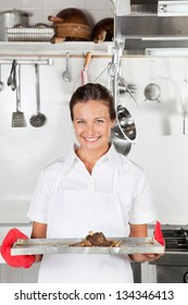 Portrait of female chef with tray of meat in restaurant kitchen