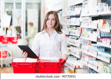 Portrait of female chemist holding tablet PC standing with basket at drugstore