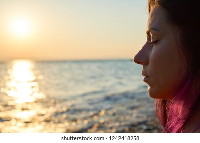 Portrait of a female with closed eyes meditating by the sea at sunrise