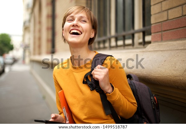 Portrait of female college student with bag laughing outside