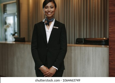 Portrait of female concierge standing at hotel reception to welcome guest. Female concierge working in hotel.