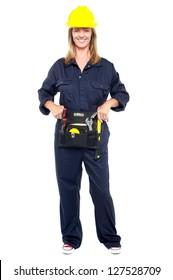 Portrait of female construction worker holding tool kit, full length shot.