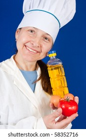 Portrait of female cook with different foods for breackfast over blue background