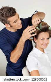 Portrait of female customer with hairstylist curling hair at beauty parlor