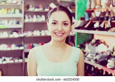 Portrait of female customer which is deciding on about pair of footwear in shoes store.