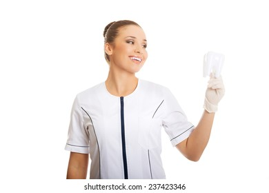 Portrait of female dentist holding a tooth model.