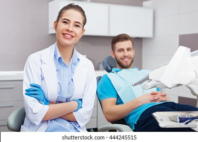 Portrait of a female dentist and young happy  male patient in a dentist office.