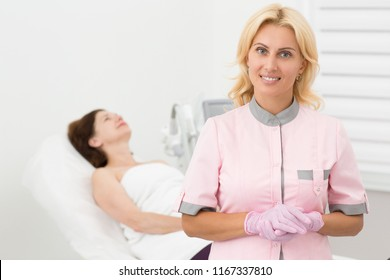 Portrait of female dermatologist during cosmetic anti aging procedure in cosmetology office. Pretty doctor posing, smiling and looking at camera. Satisfied patient lying on couch on background.