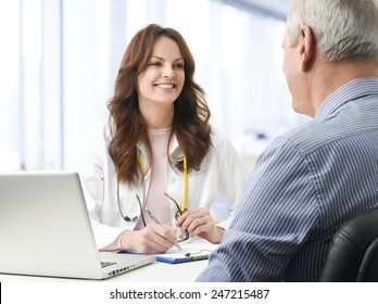 Portrait of female doctor consulting her old patient at hospital.