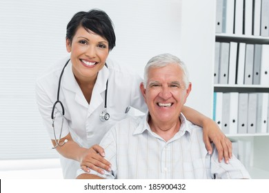 Portrait of a female doctor with happy senior patient at the hospital