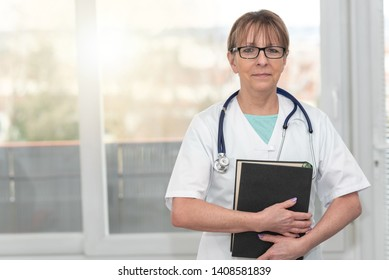 Portrait of female doctor standing and holding a medical textbook