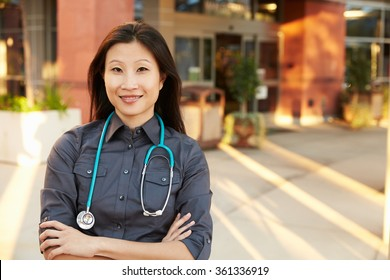 Portrait Of Female Doctor Standing Outside Hospital