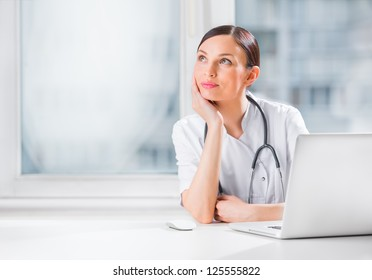 Portrait of a female doctor using her laptop computer at clinic and daydreaming
