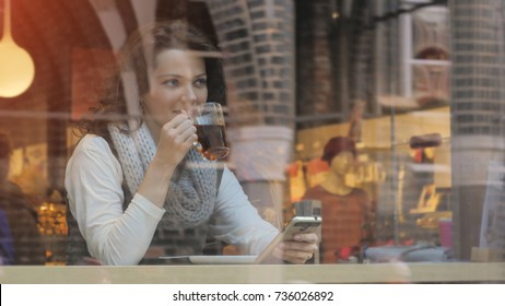 Portrait of female drinking tea and looking out of the coffee shop window