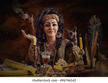 Portrait of female Egyptian psychic posing with cat figurine and occult items. The mature black haired clairvoyant sits at the desk attentively looks at the camera. Horizontal indoors shot
