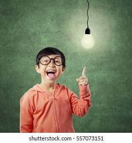Portrait of female elementary school student standing near the blackboard and pointing at light bulb. Concept of smart and creative child