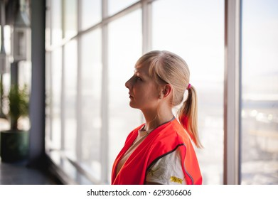 Portrait of a female employee in an orange robe vest in the working space of a production room, against a background of large windows