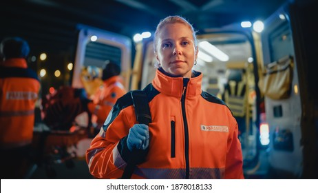 """Portrait of a Female EMS Paramedic Proudly Standing in Front of Camera in High Visibility Medical Orange Uniform with """"Paramedic"""" Text Logo. Successful Emergency Medical Technician or Doctor at Work."""