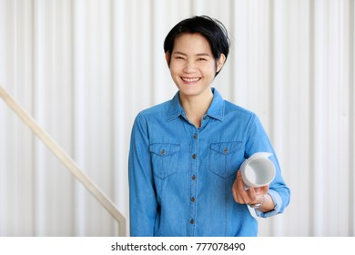 Portrait of female engineer holding roll of paper with self-confidense and friendly manner, happy woman in blue jeans suit. Looking at camera