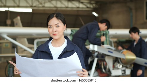 Portrait of Female engineer or pilot looking in airplane hangar to looking new aircraft drawings. Transportation and Technology concept.