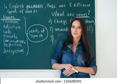 Portrait of female english teacher in front of blackboard.