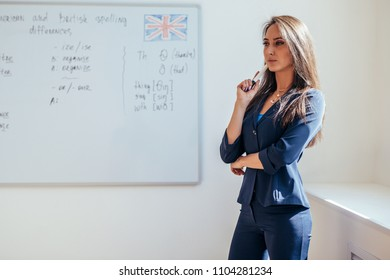 Portrait of female english teacher in front of whiteboard.