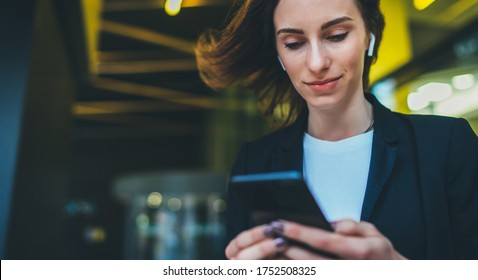 Portrait female entrepreneur in corporate suit using online banking via smartphone. Confident businesswoman texting email letter on cellphone using internet on background modern office