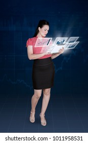 Portrait of female entrepreneur holding a digital tablet with virtual growth finance graph