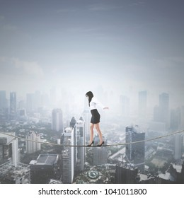 Portrait of female entrepreneur keeping her balance while walking on a rope . Shot above a city