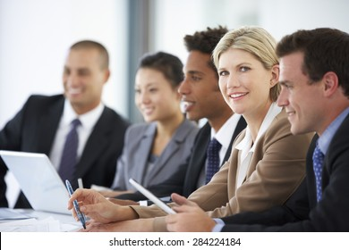 Portrait Of Female Executive Attending Office Meeting With Colleagues