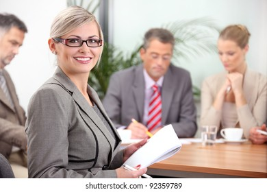 Portrait of a female executive with colleagues in the background