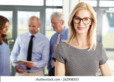 Portrait of female executive smiling while sitting at business meeting at office.