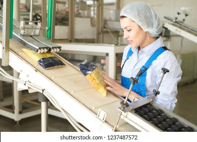 Portrait of female factory worker controlling  packaging process at modern food factory and looking at macaroni bags sliding down conveyor belt, copy space