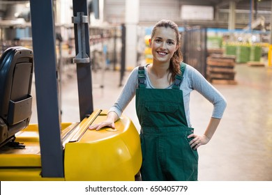 Portrait of female factory worker standing at drinks production factory