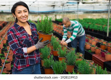 Portrait of female farmer engaged in cultivation of plants in greenhouse