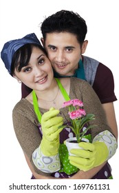 Portrait of female florist with her husband holding a flower
