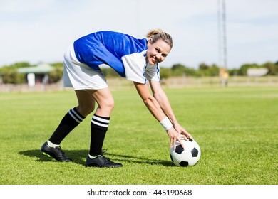 Portrait of female football player keeping a ball on the field