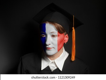 Portrait of Female french bachelor with painted France flag in Black mantle and Graduation Cap on a black background.