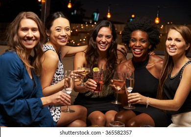 Portrait Of Female Friends Enjoying Night Out At Rooftop Bar