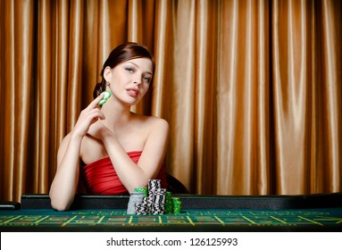 Portrait of female gambler sitting at the casino table with chips in hand