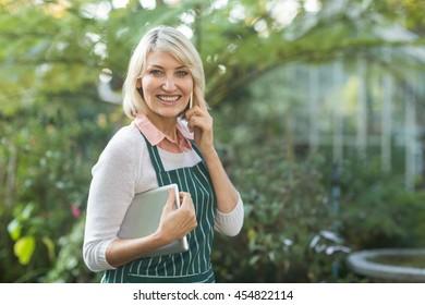 Portrait of female gardener smiling while talking on cellphone outside greenhouse