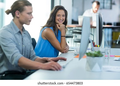 Portrait of female graphic designer sitting at desk in office