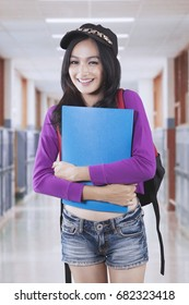 Portrait of a female high school student holding a folder while standing in the school corridor