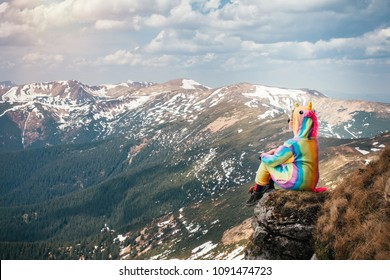 Portrait of a female hiker in a unicorn suit sitting on top of the mountain on a Carpathian landscape background on a Spring day. Wanderlust travel concept.