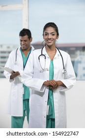 Portrait of a female Indian doctor standing in front of her colleague with a stethoscope around her neck
